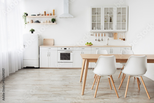 Fototapeta Scandinavian home interior. White kitchen furniture with utensils and dinner table with chairs, empty space obraz