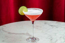Cosmopolitan Cocktail With Lime And Salted Rim On Marble Table And Red Curtain Behind