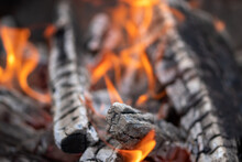 Burning Firewood Stacked In A Bonfire With Coals In The Open Air And Red Flames