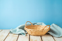 Empty Wicker Basket With Tablecloth On Rustic Table Over Blue Wall  Background.  Kitchen Mock Up For Design And Product Display.