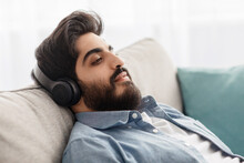 Time To Relax. Arab Guy In Wireless Headset Reclining On Sofa And Enjoying His New Stereo Headphones