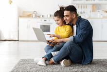 Happy Arab Man With His Little Daughter Using Laptop Together At Home