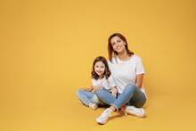 Full Body Length Happy Woman In Basic White T-shirt Have Fun Sit On Floor With Child Baby Girl 5-6 Year Old Mom Little Kid Daughter Isolated On Yellow Color Background Studio Mother's Day Love Family
