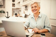 Leinwandbild Motiv Cheerful middle aged woman in casual shirt laughing, being in positive mood, using portable computer for online course. Attractive mature businesswoman working remotely from home on laptop