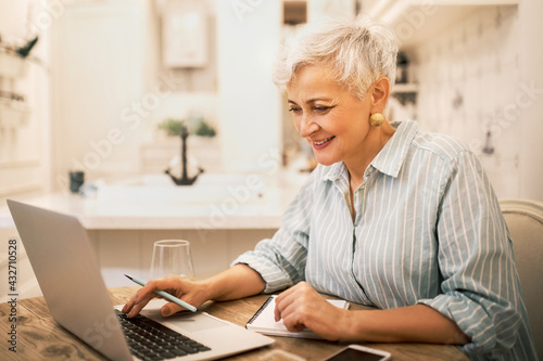 Attractive middle aged female freelancer in striped shirt sitting at home in front of open laptop, typing, working on content for website, using high speed internet connection, enjoying online work