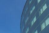 Fototapeta Londyn - Nowoczesny budynek z szklaną ścianą na tle niebieskiego nieba, Wrocław, Polska