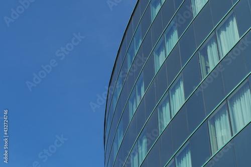 Nowoczesny budynek z szklaną ścianą na tle niebieskiego nieba, Wrocław, Polska - fototapety na wymiar