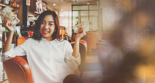 Photo Portrait beautiful woman sitting in a coffee shop, showing a five thousand baht
