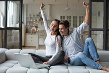 Happy Overjoyed Couple Celebrating Online Betting Bid Lottery Win Sitting On Couch At Home With Raised Hands.