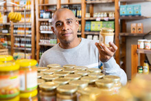 Smiling Latin American Man Choosing Foods In Supermarket, Reading Jar Contents On Label