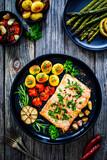Fototapeta Kawa jest smaczna - Roasted salmon steak with roast potatoes and vegetable salad served on black plate on wooden table