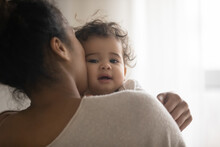 Close Up Portrait Of Young African American Mother Hold In Arms Hug Cuddle Little Ethnic Baby Girl Child. Biracial Mom Embrace Caress Lull And Kiss Small Toddler Daughter Kid. Motherhood Concept.