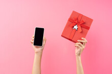 Hands Are Holding Red Gift Boxes And Phones On A Pink Background