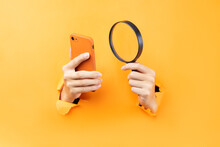 Hand Holding Magnifying Glass And Phone Protruding From Background