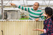 Leinwandbild Motiv Quarrel of two male and female farmers on plantation at greenhouse