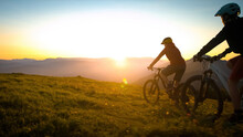 Mother And Daughter Cycling Uphill With Mountain Bikes At A Sunset.