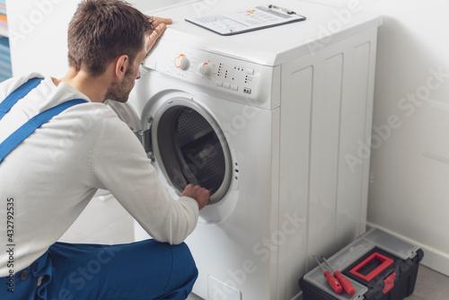 Fototapeta Technician checking a washing machine at home obraz