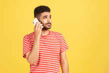 Serious Bearded Man In Red Striped T-shirt Holding Phone Near His Ear, Talking With Friends, Favorable Tariff For Calls In Roaming. Indoor Studio Shot Isolated On Yellow Background