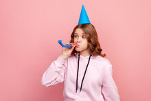 Portrait Of Funny Curly Haired Teenage Girl In Hoodie With Birthday Hat Blowing Party Pipe, Celebrating Holiday, Fooling. Indoor Studio Shot Isolated On Pink Background