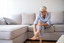 Foot Pain Leg Of Mature Woman Sitting On Sofa In The Room Holding Her Feet And Stretch The Muscles .Health Care And Spa Concept. Health Care Concept. Woman Massaging Her Painful Foot