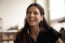 Candid Laughter. Headshot Of Overjoyed Millennial Latin Female Wearing Wired Earphones Laughing In Good Mood Showing Beautiful Even Teeth. Carefree Young Woman Having Fun Listen To Funny Joke On Radio
