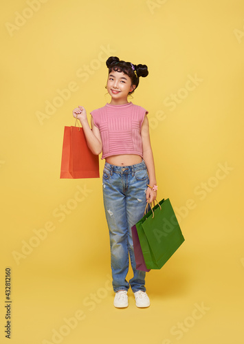 Obraz Cheerful happy kid asian child enjoying shopping, she is carrying shopping bags at the shopping center. - fototapety do salonu