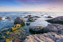 Stones On The Sea Shore In The Morning. Beautiful Summer Seascape In Purple Light. Few Clouds On The Bright Blue Sky