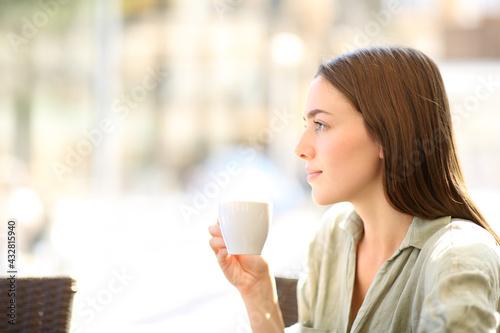 Obraz Woman drinking coffee looking away in a bar - fototapety do salonu