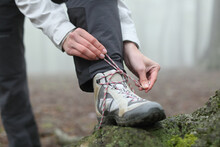 Hiker Tying Boot Laces In The Mountain