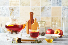 Fruit Tea With Apples And Thyme In Glass Teapot And Cup On The Kitchen Table