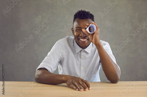 Obraz na plátne Studio portrait of happy curious black man looking with one eye through hole in paper roll