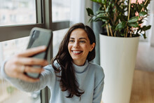 Smiling Woman Taking Selfie On A Smart Phone At Home.