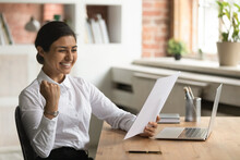 Overjoyed Smiling Indian Businesswoman Reading Good News In Letter, Sitting At Work Desk, Excited Young Woman Received Scholarship, Job Promotion Or Offer, Showing Yes Gesture, Celebrating Success