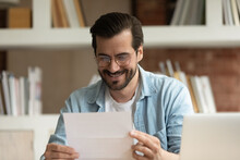 Smiling Man In Glasses Reading Good News In Letter, Sitting At Workplace, Happy Businessman Holding Document, Received Money Refund Or Job Promotion, Excited By Success, Great Exam Results