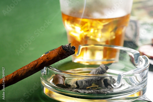 Obraz Close up of smoking cigar and whiskey glass on table - fototapety do salonu