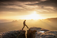 Strong Mountain Climber Hiking And Jumping Over Ridge Of A Peaks At Sunset. Man Takes Leap Of Faith