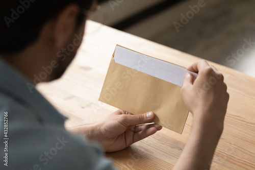Fototapeta Close up businessman opening envelope with letter, working with correspondence, paperwork, sitting at desk, manager employee unpacking bank notification or invitation, holding paper document obraz