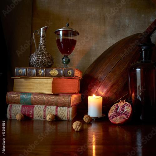 Fototapeta Fotografia jak malarstwo olejne przedstawiająca martwą naturę ze starymi książkami, kieliszkiem czerwonego wina, lutnią gitarową i owocem granatu w stylu starych mistrzów malarstwa holenderkiego. obraz