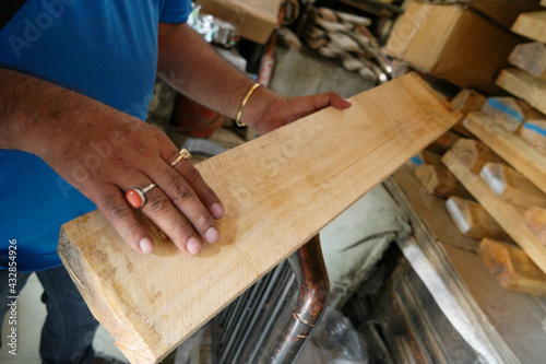 Foto Closeup shot of the hands of a male holding the board in a factory for a cricket