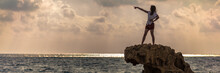 Panoramic Shot Of A Woman Standing On A Cliff Proudly And Pointing At The Sea In Paphos, Cyprus