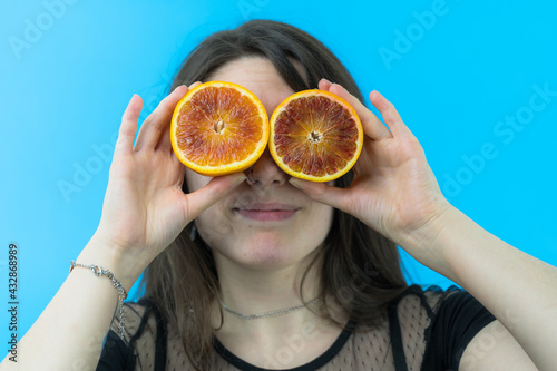 Valokuvatapetti Una giovane e bella ragazza si diverte usando un arancia rossa tagliata a metà c