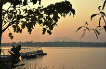 A Beautiful View Of A Lake With A Mountain Far Away With Trees In Foreground During Sunset