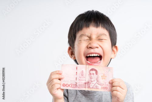 Canvas Print Asian boy holding Thai money or 100 baht banknote with big smile