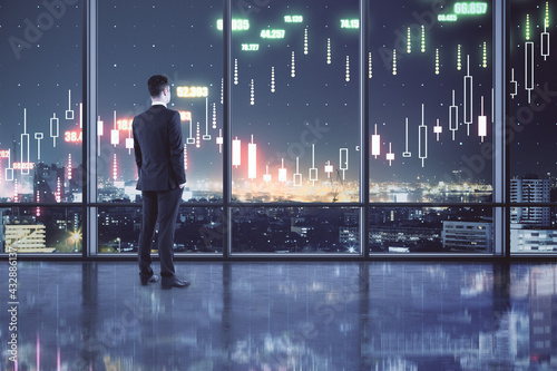 Fotografia Profitable investing concept with buisnessman in spacious hall looking at night city and digital screen with financial chart candlestick