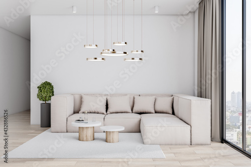 Fototapeta Sunny spacious living room with huge big sofa and stylish coffee tables on wooden floor, green plant in black vase and city view from windows to floor. obraz