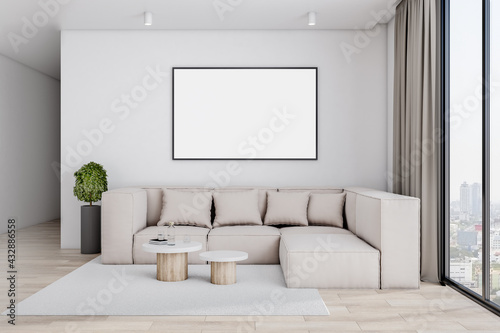 Fototapeta Blank white poster on the center of light wall in stylish living room with big beige sofa, cashmere carpet on wooden floor and city view from big window. 3D rendering, mock up obraz
