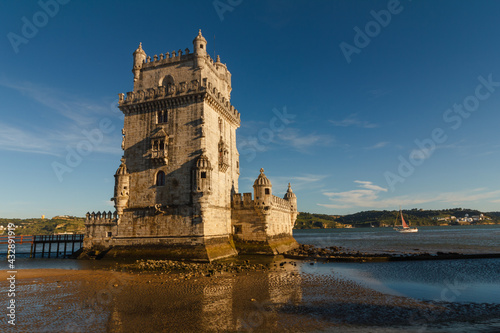 Belem Tower is a fortified tower on the Tagus river at sunset. Lisbon. Portugal. UNESCO World Heritage Site. Top tourist attraction in Europe. Concept of travel and tourism. #432891919
