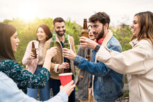 Group Of Friends Gathering Outdoors Drinking Beers And Talking Together