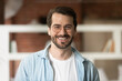 Leinwandbild Motiv Head shot portrait confident smiling bearded businessman in glasses looking at camera, standing in office, successful happy young man employee entrepreneur posing for photo or recording video