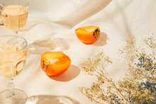 Halfs Of Persimmon Fruits And Two Glasses With Lemonade On Pastel Background With White Cloth And Sunlit. Summer Drinks And Refreshment Concept. Minimal Style Composition.
